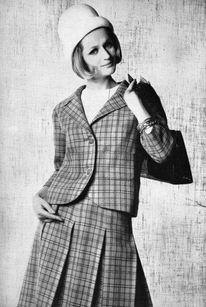 A box pleat skirt in blue plaid wool worn with a matching jacket and a white felt cloche hat and white sleeveless blouse, by Belinda Belville and worn by a model who looks remarkably like Glenn Close. The bangles are by Christian Dior. Date: 1962