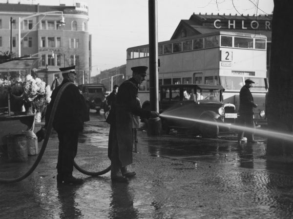 Cleaning the market place with a hose and water in Berlin, Germany in the 1930s