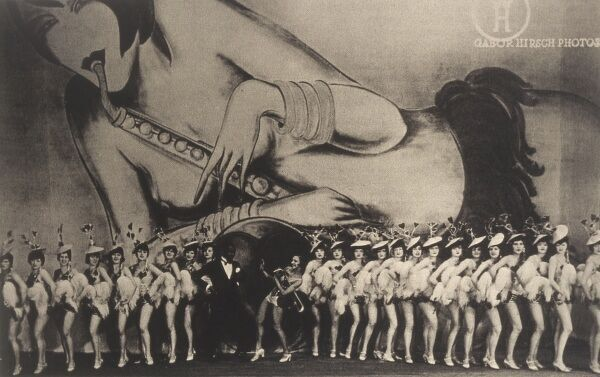 A line of showgirls pose for the camera in front of a large poster of a scantily clad girl playing the saxophone Date: 1927