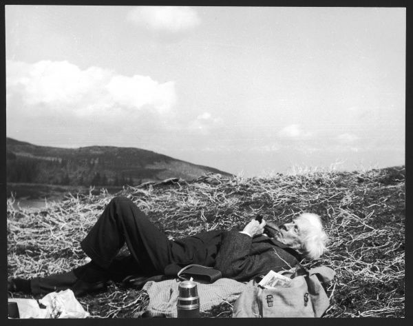 BERTRAND RUSSELL, 3rd Earl Russell - British philospher and author, lying down smoking a pipe during one of his hikes into the Welsh countryside. Date: 1872 - 1970