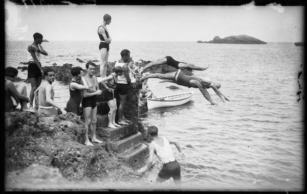 Young people bathing and diving off the rocks into the sea at Biarritz, France