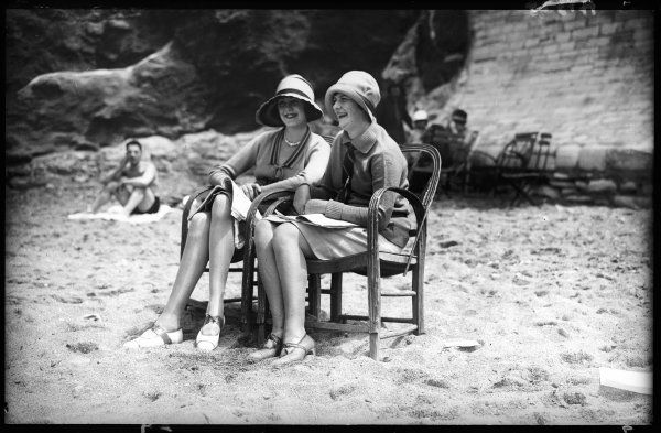 Two trendy young women (with an admirer in the background) enjoy posing on the beach at Biarritz, France