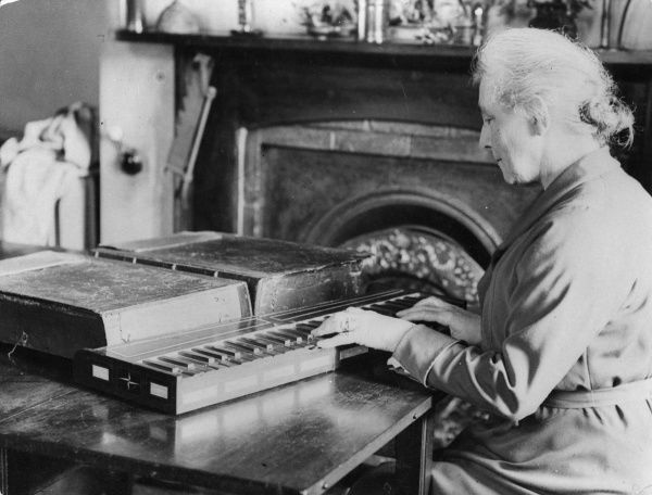 Mrs Galpin plays a remarkable 17th century organ and bellows, with a case made from an old bible. Part of an collection of over 600 musical instruments, Essex, England. Date: 1930s