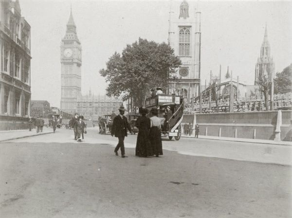 Street scene near Big Ben, the Houses of Parliament and St Margaret's Church, in Central London. An open-topped omnibus goes past, and various pedestrians cross the road. It is just after 3.30 in the afternoon. Date: early 20th century