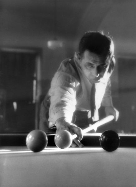 A billiards player concentrates on his game. Date: 1930s