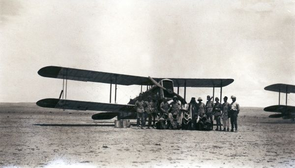 A biplane in the desert with crew and arabs, somewhere in Iraq