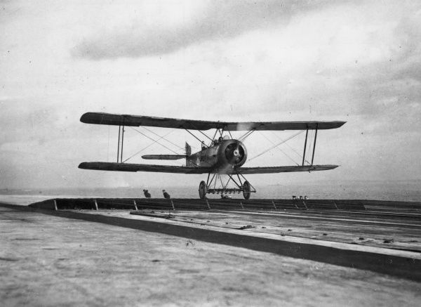 A biplane coming in to land on the flight deck of HMS Argus, one of the first aircraft carriers, launched 1917, during the First World War. Date: circa 1917-1918