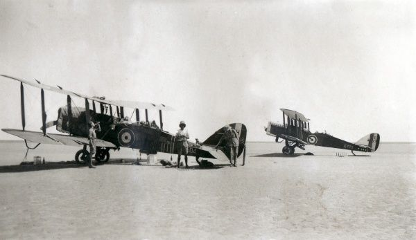 Two biplanes in the desert with their crew resting and drinking, somewhere in Iraq
