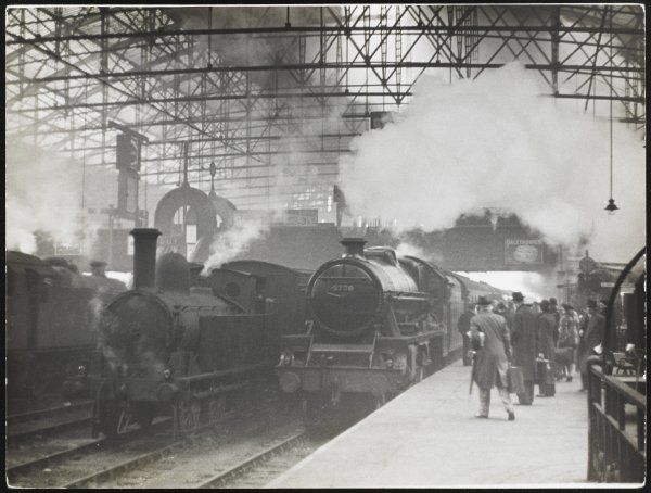 Passengers move towards the L.M.S. London Express, as it approaches the platform at Birmingham station