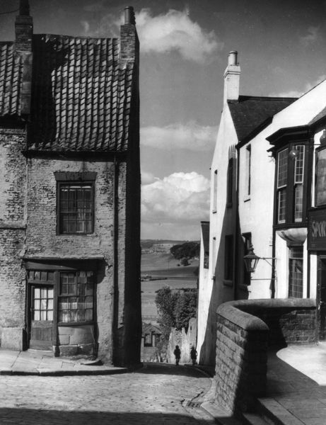 A quaint old shop front in a steep, cobbled corner of Bishop Auckland, County Durham, England. Date: 1950s