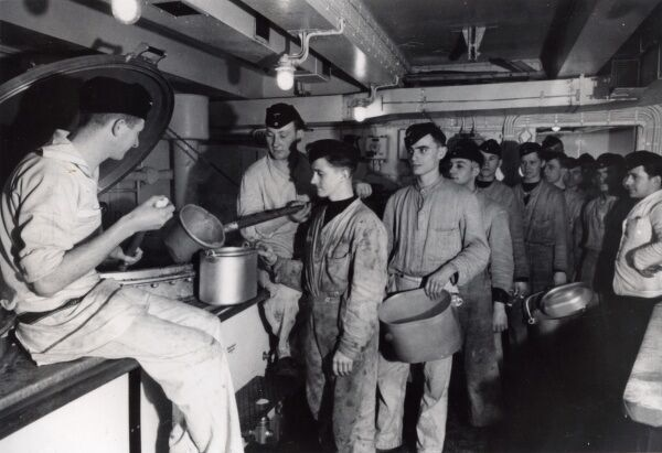 The caboose or crew's galley where the food server ladles hot food from giant cauldrons into pots which are then delivered to the mess decks on the Battleship Bismarck Date: c. 1941