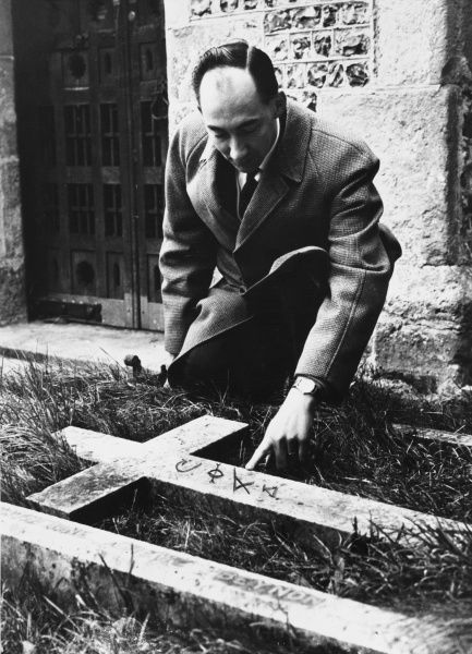 A paranormal investigator discovers Black Magic chalk marks on a grave cross, following a Black Magic raid on a country church at Alfriston, Sussex, England. Date: 1960s