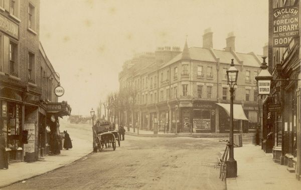 A photograph looking up Tranquil Vale showing the now very busy junction as a wide empty road with a few horses and carts. A Penny Farthing leans against a lamp post