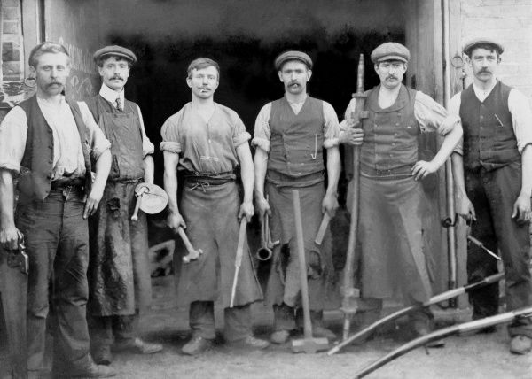 A superb photograph of six Blacksmiths and coachbuilders posing for a photograph outside their forge/workshop, each holding the tools of their trade