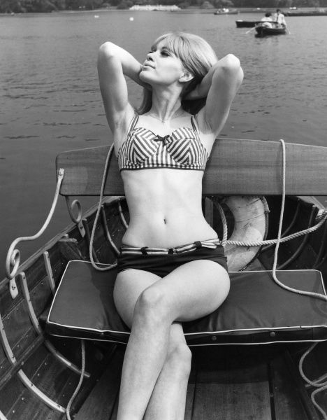 Female model in a bikini in a rowing boat, her arms behind her head in a relaxed pose. Date: 1960s