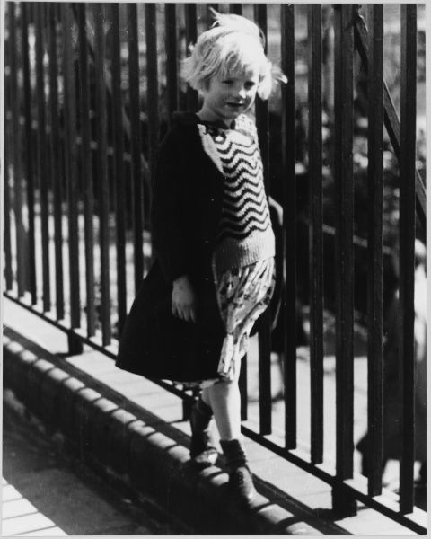 A little girl with blond hair walks along the pavement holding on to the railings