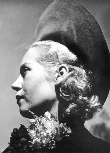 A blonde woman models a fashionable velvet hat with a wide brim