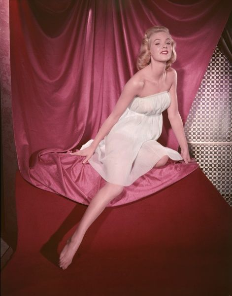 Fifties blonde bombshell, in a strapless accordian pleated chemise, kneels on pink satin & points her shapely leg at the floor. Her head is tilted backwards