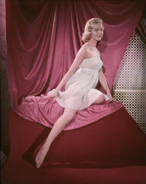 Fifties blonde bombshell, in a strapless accordian pleated chemise, kneels on pink satin & points her shapely leg at the floor
