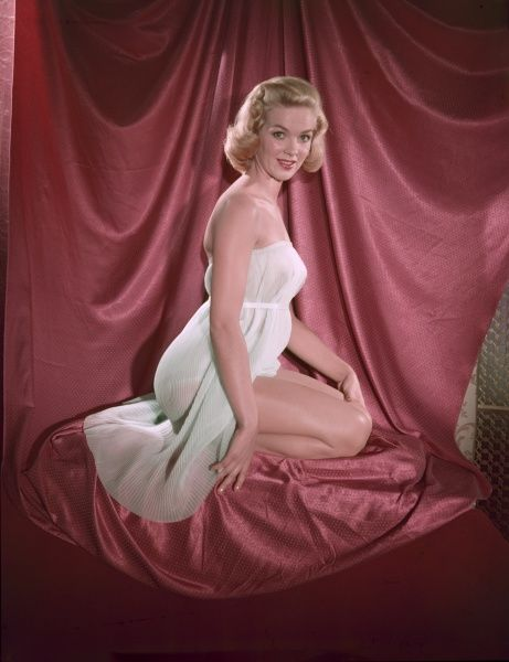 Fifties blonde bombshell, in a strapless accordian pleated chemise, kneels in profile on pink satin