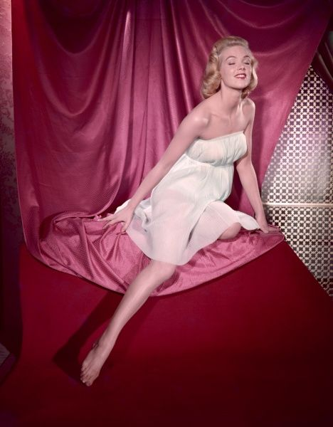 Fifties blonde bombshell, in a strapless accordian pleated chemise, kneels, with eyes closed, on pink satin & points her shapely leg at the floor