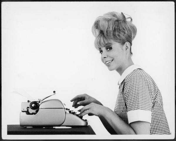 An attentive blonde typist or secretary, poised for dictation over the keyboard of her typewriter