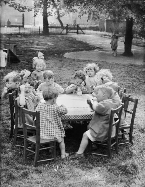 A group of orphan children blowing bubbles around a table in the gardens of the Foundling Hospital, Guildford Street, London, England