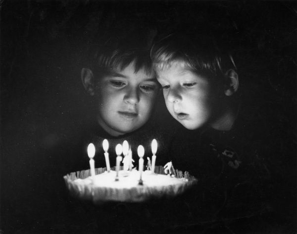 Two boys around a birthday cake, one of them about to blow out the candles