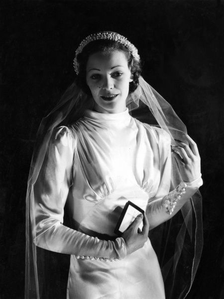 The blushing, fashionable bride, playing demurely with her veil, prayer book in hand. Date: 1930s