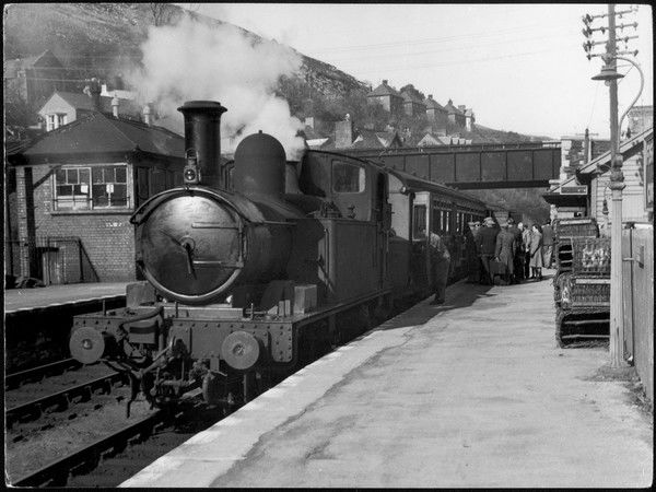 People board a steam train waiting in the station
