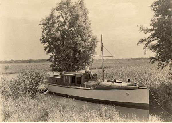 View over the Norfolk Broads in East Anglia showing a boat stationery in the water on a lovely, sunny day with a woman sitting on top of the cabin enjoying the sun's rays