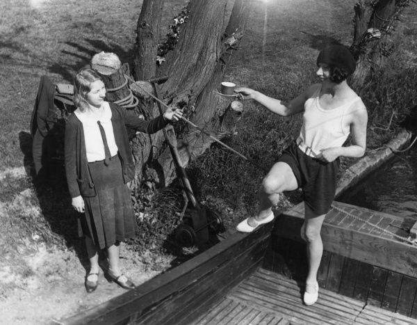 A jolly young woman, wearing a beret, offers a cup and saucer of tea from the deck of her moored boat to another young woman wearing a box pleated skirt beside a tree trunk! Date: 1930s