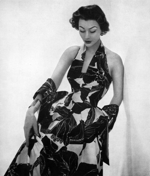 An evening dress with a plunging halter neck-line and full, swirling skirt made from a tropical flower print Ever-glaze cotton. Date: 1953