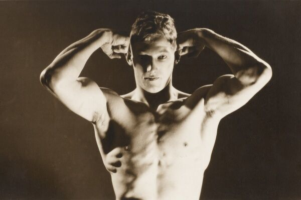 A very well-lit shot of an English strongman flexing his biceps and upper torso