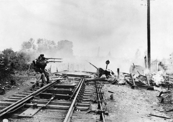 Scene during the Bombardment of Termonde, Belgium, by the Germans during the First World War. Showing Belgian infantry sniping after blowing up the railway. Date: 18 September 1914