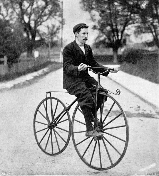 Photograph of a cyclist on a 'Bone Shaker' bicycle of the 1840's to 1850's. This type of bicycle was innovative in having pedals, but earnt it's moniker through the used of solid wood or metal wheels