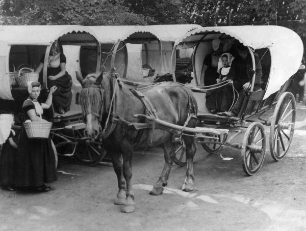 Dutch women driving to market in their horse-drawn 'bonnet' carts, which have the same shape as their own bonnets! Our pictures shows the bonnet cart park! Date: 1930s
