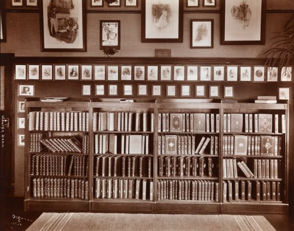 Walter Dunn. Bookcase in an office of Walter Dunn, publisher; books with elaborate covers fill the case, framed illustrations on the wall