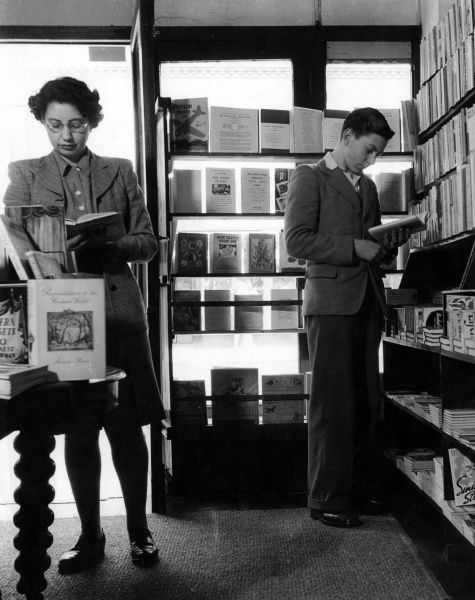 A middle-aged woman and young man, bookworms, browsing in a book shop. Date: 1940s