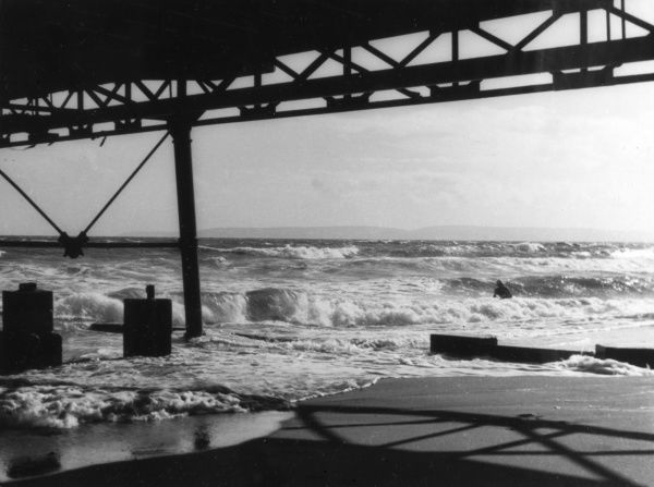 A rough sea scene, taken from under the pier at Boscombe, Hampshire, England. One brave swimmer is braving the waves and Purbeck Hill is in the distance. Date: 1930s