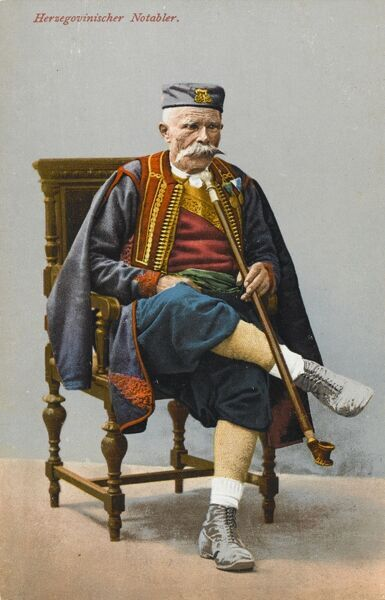 Bosnia & Herzegovina - Traditional Dress (1 of 3) - A notable Herzegovinan Gentleman with a remarkably long pipe, seated on a finely turned wooden chair