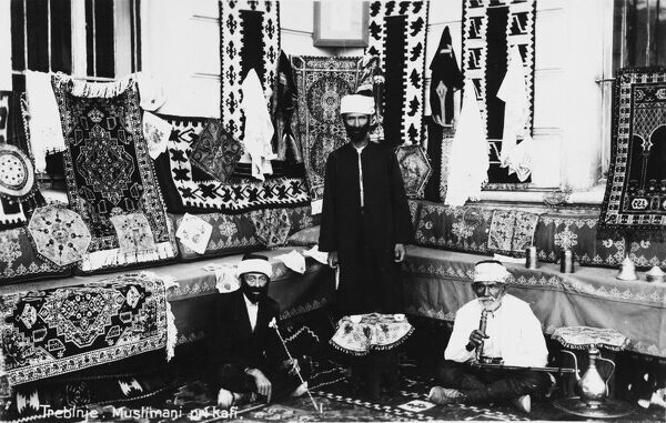 Bosnia Herzegovina - Trebinje. A group of Muslim Carpet and Textile sellers - two are seated and smoking a Hookah Pipe