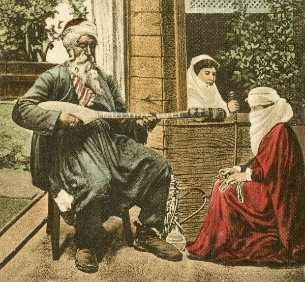 Musician playing to two Turkish women in Bosnia on a summer's evening