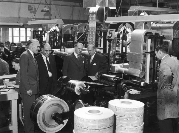 Four clearly rather important men (company directors?) visit, or possibly inspect, a printing works. The job at hand at the time of this photograph was the production of wrappers for Penguin chocolate bars. Photograph by Heinz Zinram