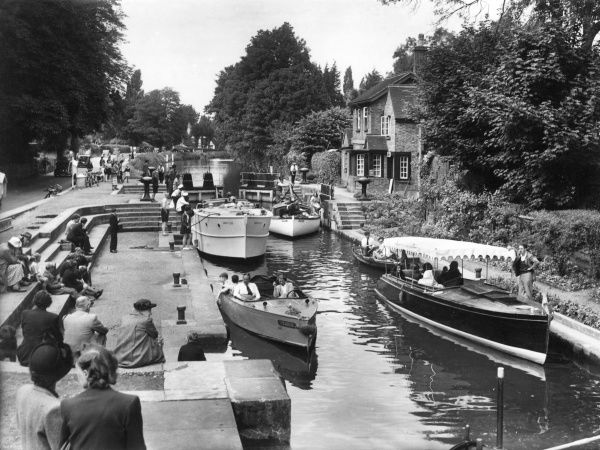 A lovely scene of boats passing through Boulters Lock, a beautifully wooded section of the River Thames, between Marlow and Maidenhead, Buckinghamshire, England. Date: circa 1950