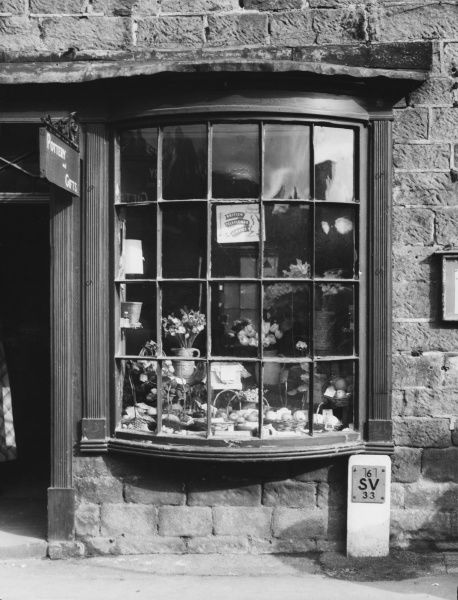 The lovely old fashioned bow- fronted window of the pottery and gifts shop in Cromford, Derbyshire, England