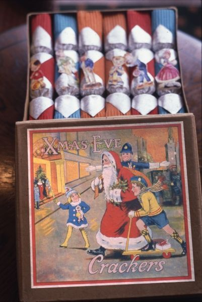 A lovely box of Christmas crackers from the 1920s, with the contents intact and the box lid featuring a bright and jolly picture of Father Christmas being helped to cross the road by a policeman and two children