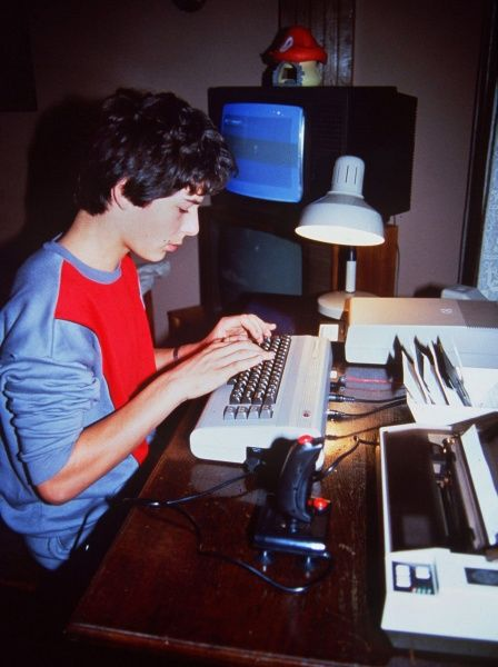 A boy sits at a desk typing on his Commodore 64 keyboard. A printer, joystick and lamp sit on the desk. Two televisions and a strange model of a mushroom are in the background