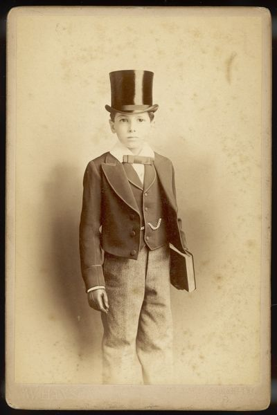 Boy wearing an Eton suit comprised of short single- breasted jacket & waistcoat with roll collar, light grey trousers, white Eton collar & narrow bowtie & a top hat
