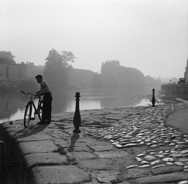 A boy and his bicycle on the banks of the River Severn at Bewdley Bridge, Worcestershire. Photograph by Norman Synge Waller Budd